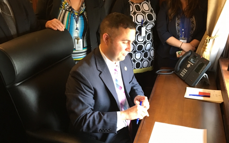 Rep. Soto signs ASPIRE Act as staff watches.